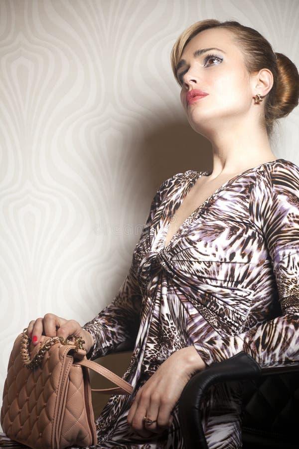 Νέα γυναίκα μόδας με την τσάντα στην ταπετσαρία στοκ εικόνες