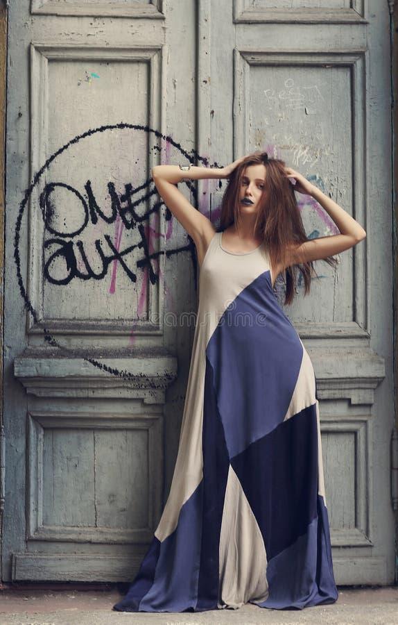 Νέα γυναίκα μόδας που στέκεται κοντά στην παλαιά ξύλινη πόρτα με τα γκράφιτι στοκ εικόνα