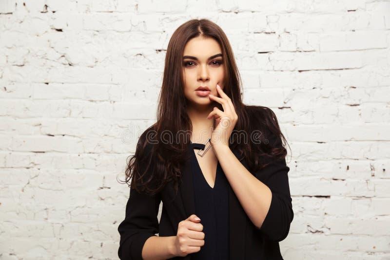 Νέα γυναίκα μόδας στο μαύρο σακάκι δίπλα στο τουβλότοιχο στοκ εικόνες