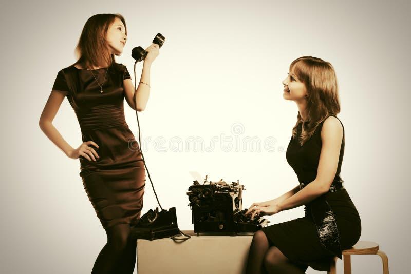 Νέα γυναίκα μόδας δύο με το αναδρομικές τηλέφωνο και τη γραφομηχανή στοκ εικόνα