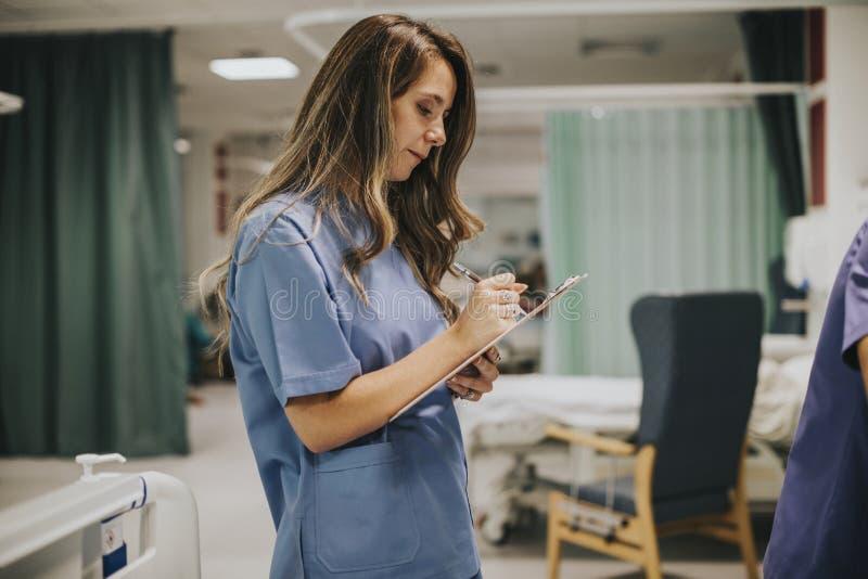Νέα γυναίκα νοσοκόμα που παίρνει τις σημειώσεις στοκ εικόνες με δικαίωμα ελεύθερης χρήσης