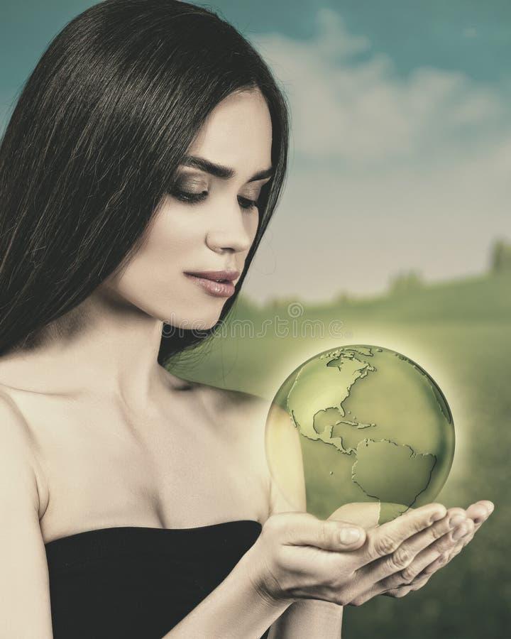 Νέα γυναίκα ομορφιάς με τη γήινη σφαίρα στοκ φωτογραφία με δικαίωμα ελεύθερης χρήσης