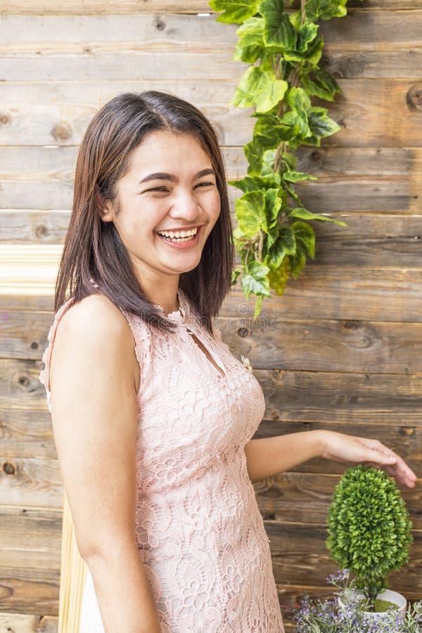 Νέα γυναίκα ομορφιάς που χαμογελά ενάντια σε έναν ξύλινο τοίχο στοκ εικόνα