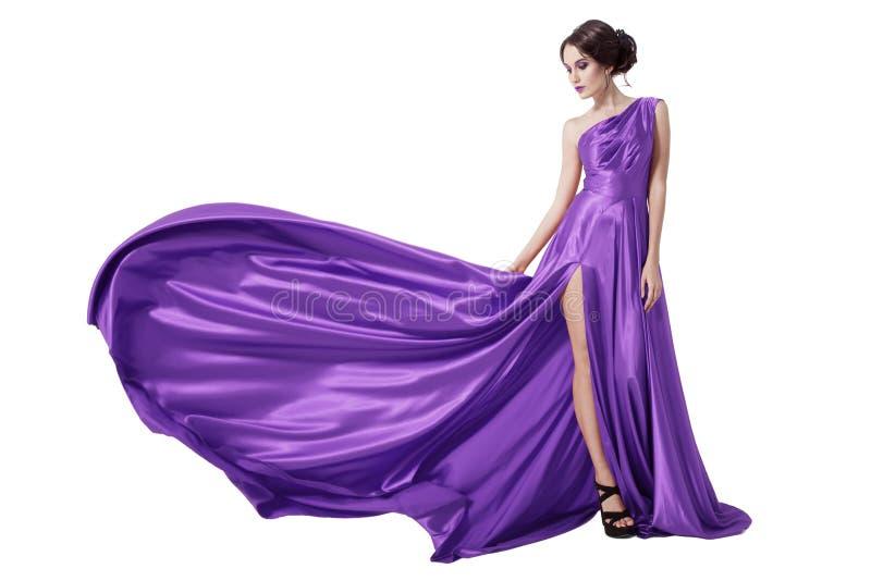 Νέα γυναίκα ομορφιάς στο κυματίζοντας ιώδες φόρεμα. Απομονωμένος στοκ εικόνα