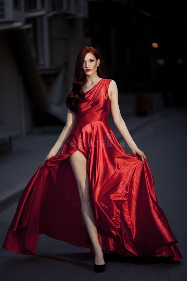 Νέα γυναίκα ομορφιάς στο κόκκινο φόρεμα υπαίθριο στοκ εικόνα