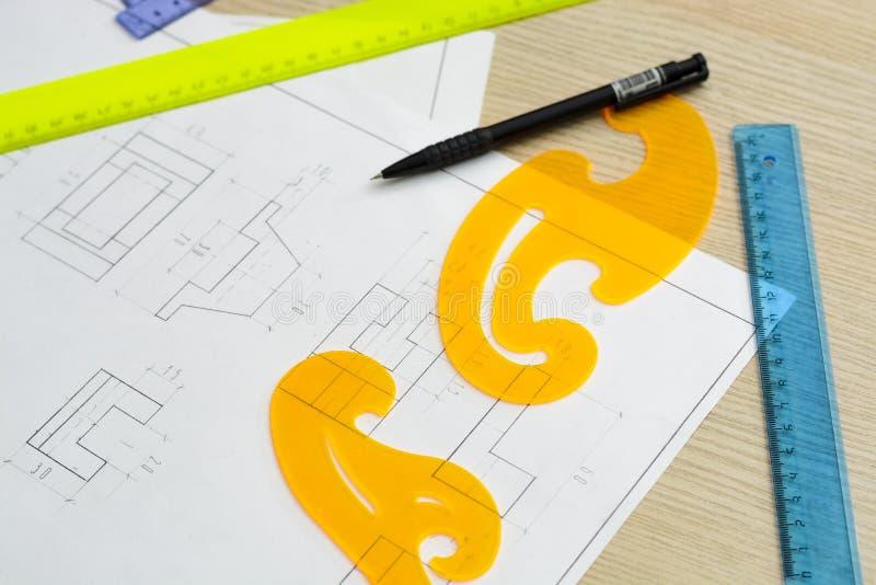 Νέα γυναίκα - ο αρχιτέκτονας σύρει ένα σχέδιο, γραφικό, σχέδιο, γεωμετρικές μορφές από το μολύβι στο μεγάλο φύλλο του εγγράφου στ στοκ εικόνες με δικαίωμα ελεύθερης χρήσης