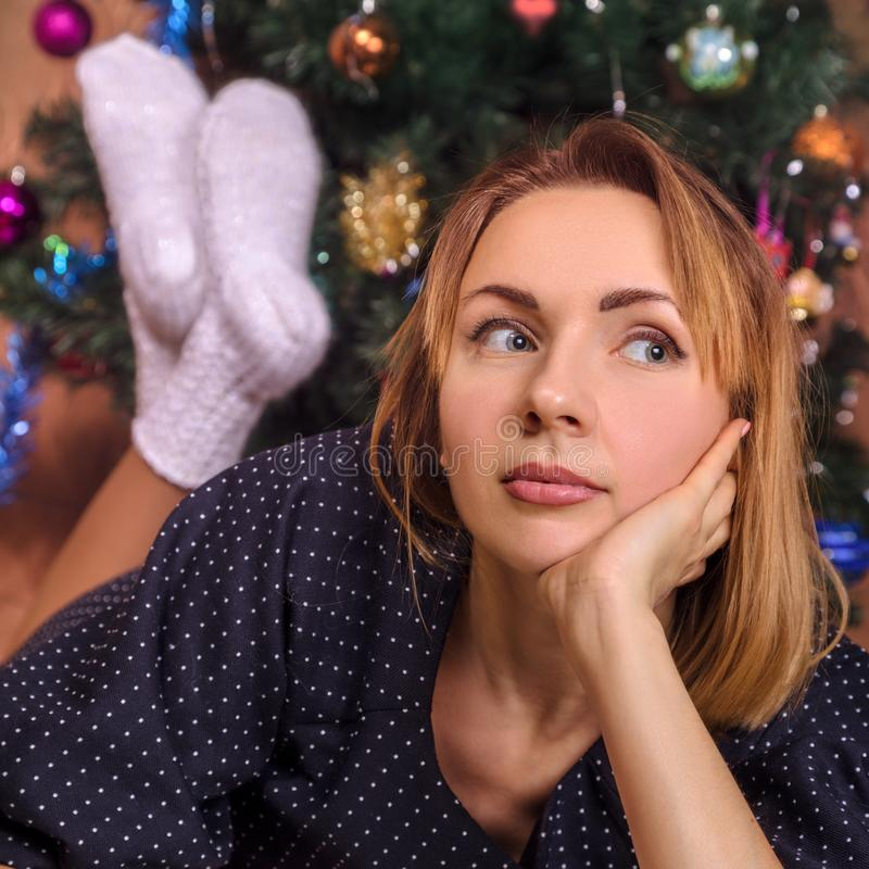 Νέα γυναίκα πλησίον του χριστουγεννιάτικου δέντρου στοκ φωτογραφίες