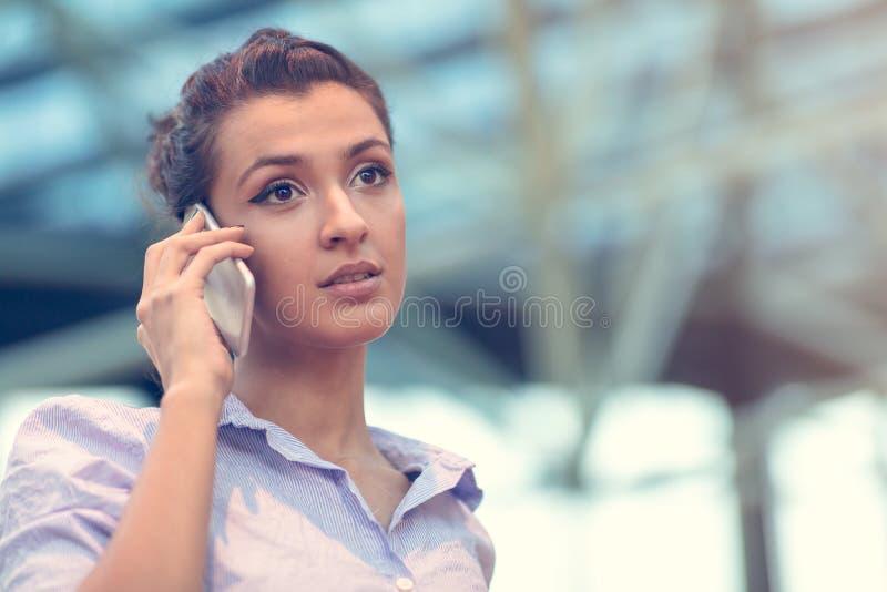 Νέα γυναίκα πολυάσχολη με την κλήση, που κουβεντιάζει στο πορτρέτο τηλεφωνικής πλάγιας όψης κυττάρων στοκ φωτογραφίες