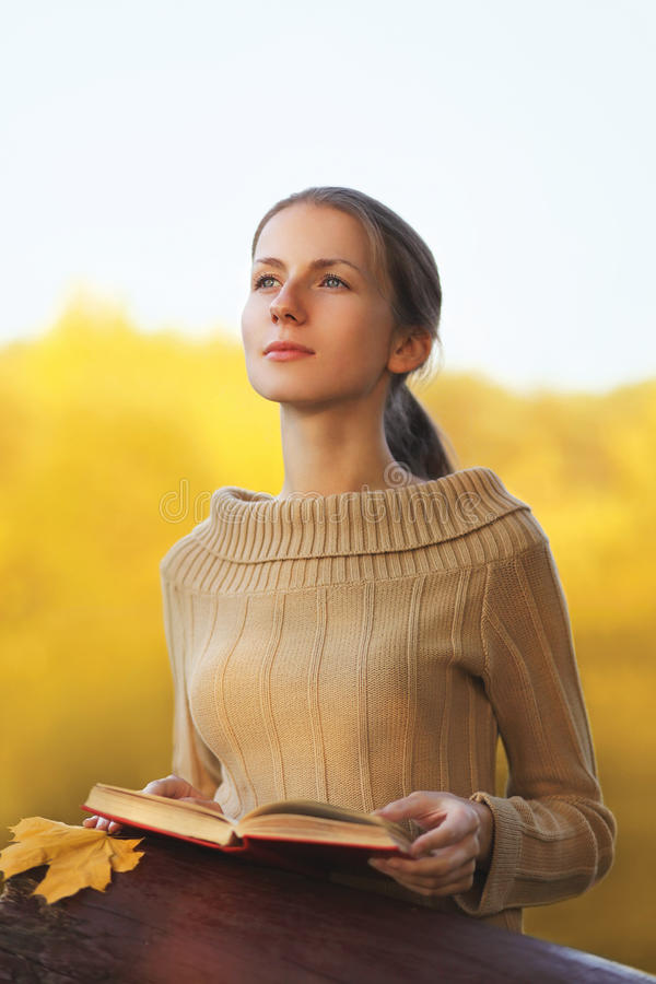 Νέα γυναίκα πορτρέτου με το βιβλίο και κίτρινα όνειρα φύλλων σφενδάμου υπαίθρια το θερμό ηλιόλουστο φθινόπωρο στοκ εικόνες
