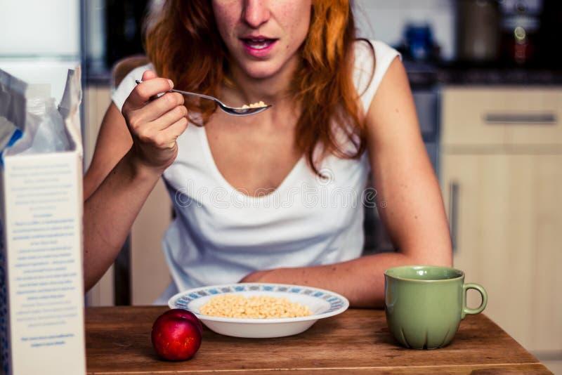 Νέα γυναίκα που έχει τα δημητριακά και τα φρούτα για το πρόγευμα στοκ φωτογραφία με δικαίωμα ελεύθερης χρήσης