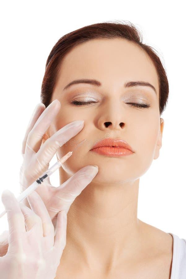 Νέα γυναίκα που έχει την καλλυντική έγχυση botox στοκ εικόνες