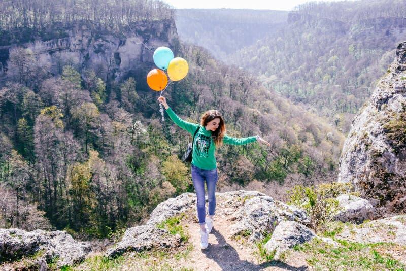 Νέα γυναίκα που έχει τη διασκέδαση με τα χρωματισμένα μπαλόνια στην άκρη του απότομου βράχου στα ρωσικά βουνά στοκ εικόνες με δικαίωμα ελεύθερης χρήσης