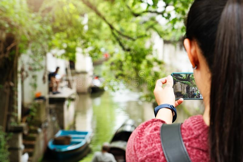 Νέα γυναίκα που έχει τη διασκέδαση στην τοπική πόλη καναλιών στην Κίνα με τη κάμερα στο smartphone που κάνει τις εικόνες στοκ εικόνα με δικαίωμα ελεύθερης χρήσης