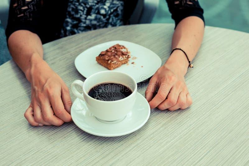 Νέα γυναίκα που έχει τον καφέ και το κέικ στοκ φωτογραφία