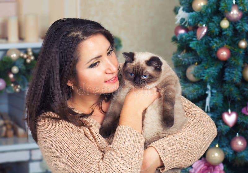 Νέα γυναίκα που αγκαλιάζει τη γάτα στοκ εικόνα