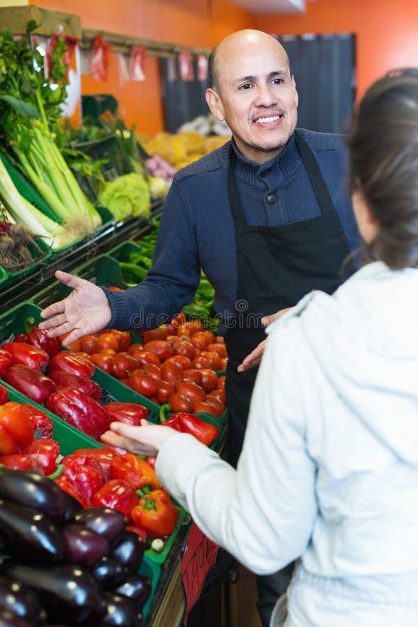 Νέα γυναίκα που αγοράζει τα εποχιακά λαχανικά στο παντοπωλείο από το ώριμο SE στοκ εικόνες με δικαίωμα ελεύθερης χρήσης