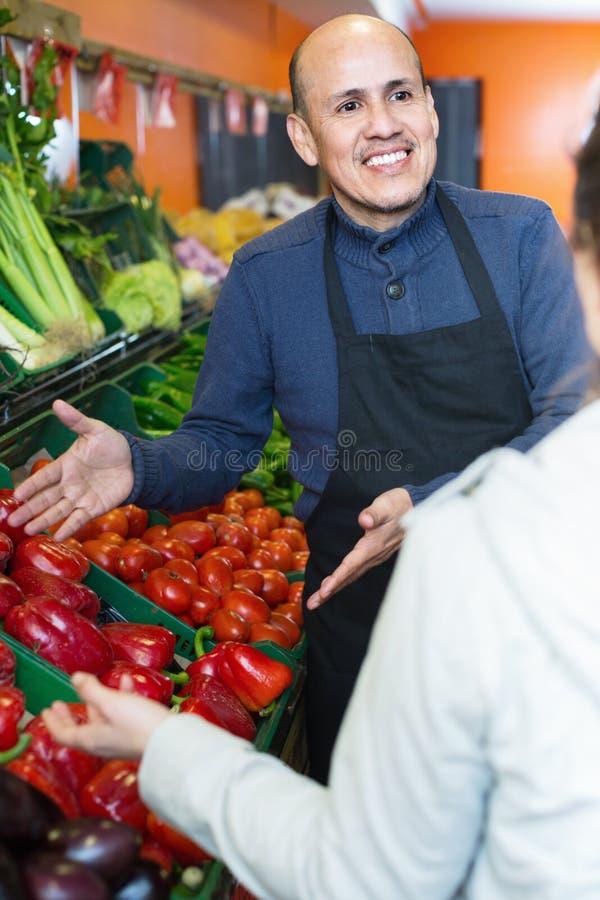 Νέα γυναίκα που αγοράζει τα εποχιακά λαχανικά στο παντοπωλείο από το ώριμο SE στοκ φωτογραφία με δικαίωμα ελεύθερης χρήσης