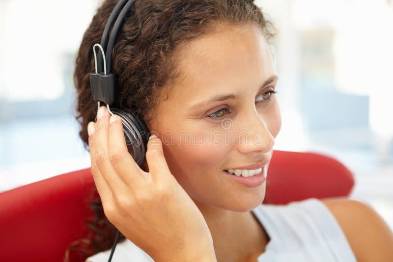 Νέα γυναίκα που ακούει τα ακουστικά στοκ εικόνα