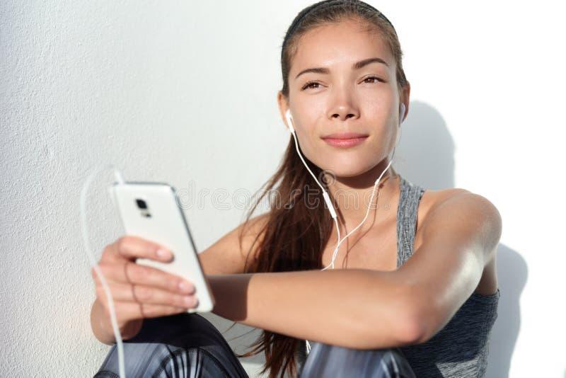 Νέα γυναίκα που ακούει τη μουσική κινήτρου με τα ακουστικά στο έξυπνο τηλέφωνο app στοκ φωτογραφία με δικαίωμα ελεύθερης χρήσης