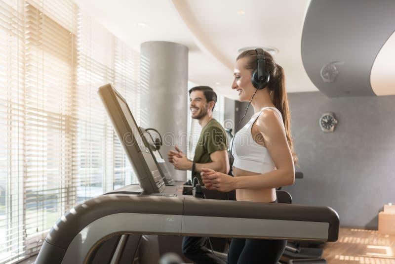 Νέα γυναίκα που ακούει τη μουσική τρέχοντας σύγχρονο treadmill στοκ εικόνες με δικαίωμα ελεύθερης χρήσης