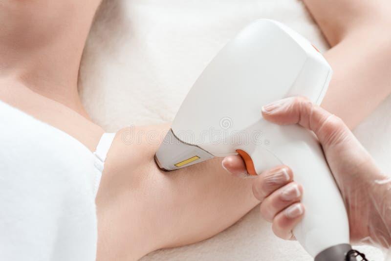 Νέα γυναίκα που λαμβάνει το epilation αφαίρεσης τρίχας λέιζερ στη μασχάλη στοκ φωτογραφίες με δικαίωμα ελεύθερης χρήσης