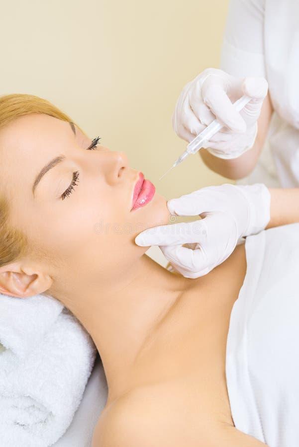 Νέα γυναίκα που λαμβάνει botox την έγχυση στα χείλια στοκ φωτογραφία με δικαίωμα ελεύθερης χρήσης