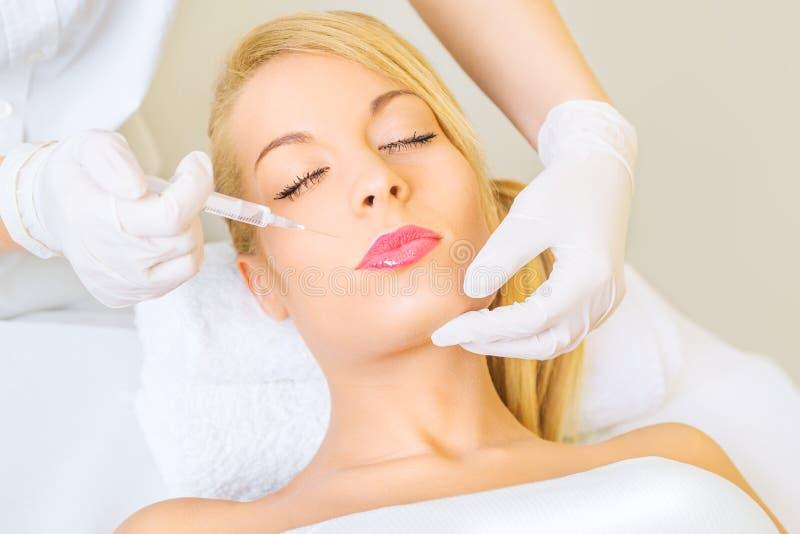 Νέα γυναίκα που λαμβάνει botox την έγχυση στοκ εικόνα