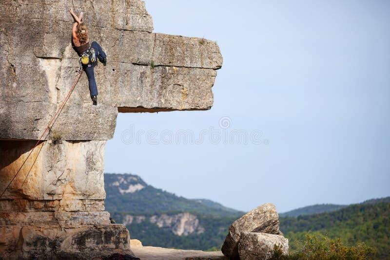 Νέα γυναίκα που αναρριχείται σε έναν απότομο βράχο στοκ εικόνα
