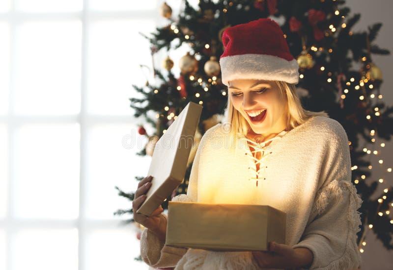 Νέα γυναίκα που ανοίγει ένα παρόν στο πρωί Χριστουγέννων στοκ φωτογραφία με δικαίωμα ελεύθερης χρήσης