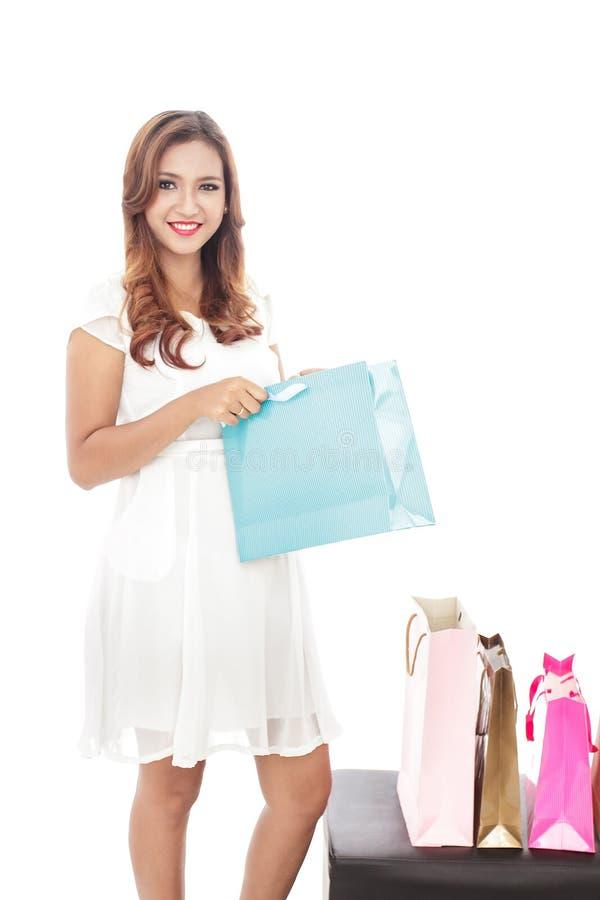 νέα γυναίκα που ανοίγει μια τσάντα αγορών στεμένος δίπλα στον ομο στοκ φωτογραφίες