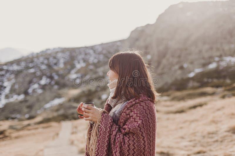 Νέα γυναίκα που απολαμβάνει τη φύση στο βουνό που καλύπτεται με ένα κάλυμμα και ένα καυτό ποτό κατανάλωσης σε μια κούπα r r στοκ φωτογραφία με δικαίωμα ελεύθερης χρήσης