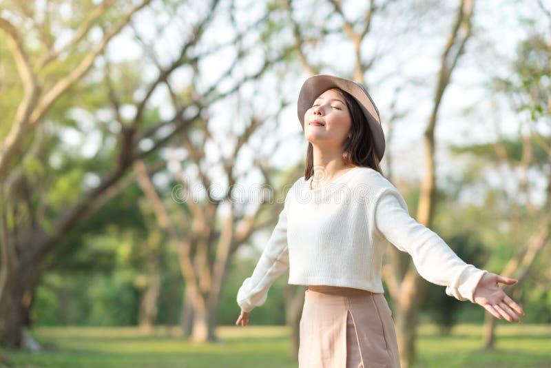Νέα γυναίκα που απολαμβάνει το φως πρωινού σε ένα πάρκο στοκ εικόνες