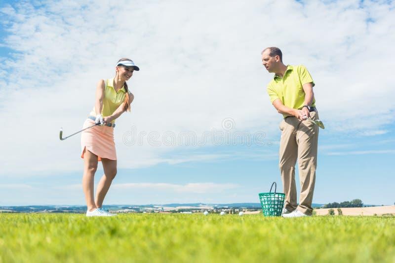 Νέα γυναίκα που ασκεί τη σωστή κίνηση κατά τη διάρκεια της κατηγορίας γκολφ στοκ εικόνες