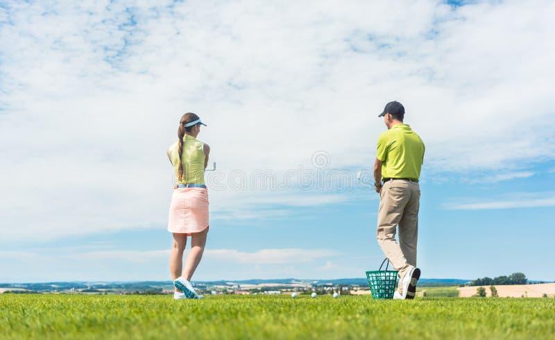 Νέα γυναίκα που ασκεί τη σωστή κίνηση κατά τη διάρκεια της κατηγορίας γκολφ υπαίθρια στοκ εικόνες με δικαίωμα ελεύθερης χρήσης