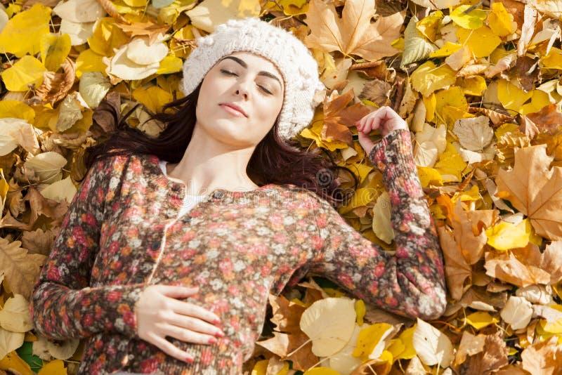 Νέα γυναίκα που βάζει στα φύλλα φθινοπώρου στοκ φωτογραφίες