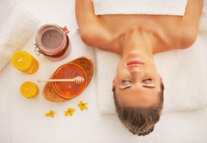 Νέα γυναίκα που βάζει στον πίνακα μασάζ έτοιμο για τη θεραπεία μελιού στοκ εικόνες με δικαίωμα ελεύθερης χρήσης
