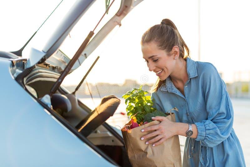 Νέα γυναίκα που βάζει τα παντοπωλεία στον κορμό αυτοκινήτων στοκ εικόνα με δικαίωμα ελεύθερης χρήσης