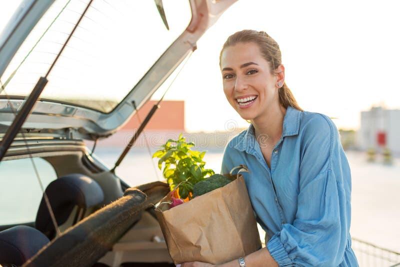 Νέα γυναίκα που βάζει τα παντοπωλεία στον κορμό αυτοκινήτων στοκ εικόνες