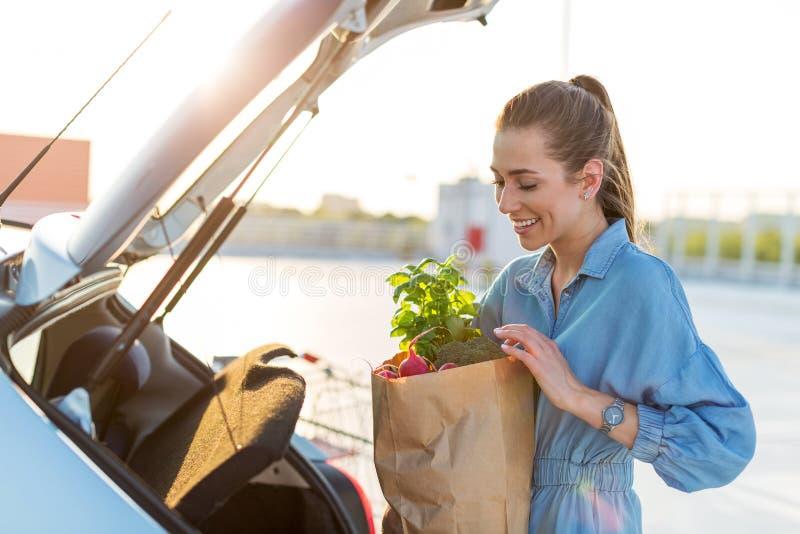 Νέα γυναίκα που βάζει τα παντοπωλεία στον κορμό αυτοκινήτων στοκ φωτογραφία