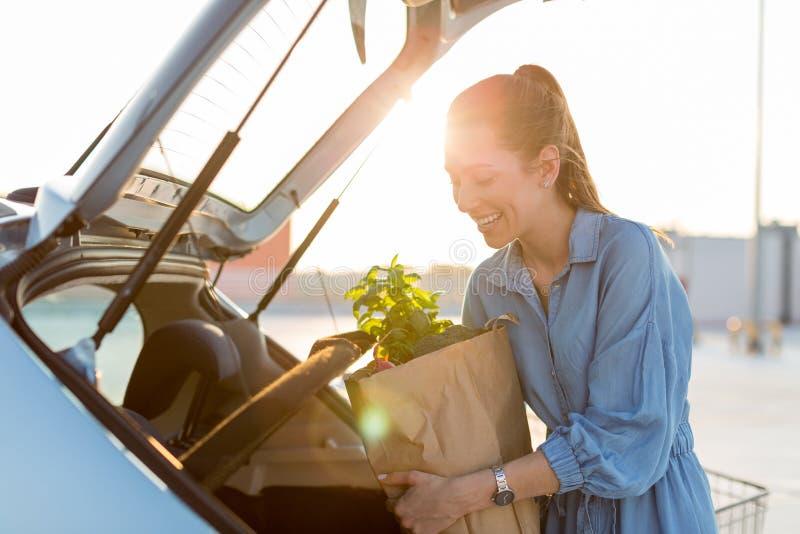 Νέα γυναίκα που βάζει τα παντοπωλεία στον κορμό αυτοκινήτων στοκ εικόνα