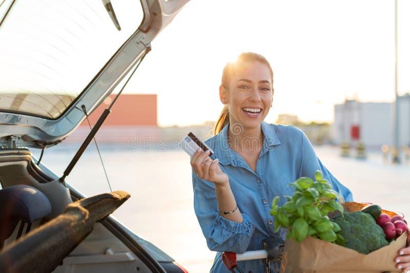 Νέα γυναίκα που βάζει τα παντοπωλεία στον κορμό αυτοκινήτων στοκ φωτογραφία με δικαίωμα ελεύθερης χρήσης