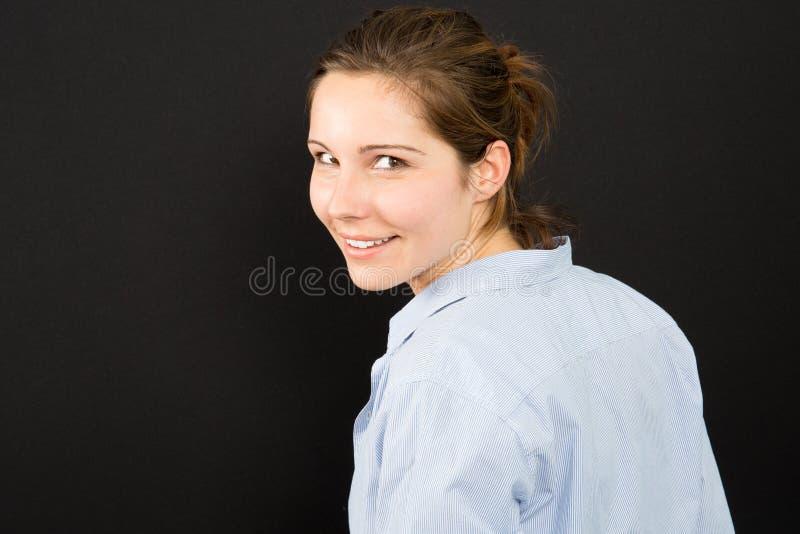 νέα γυναίκα που βλέπει από την τριών τετάρτων πλάτη που γυρίζει στοκ φωτογραφία