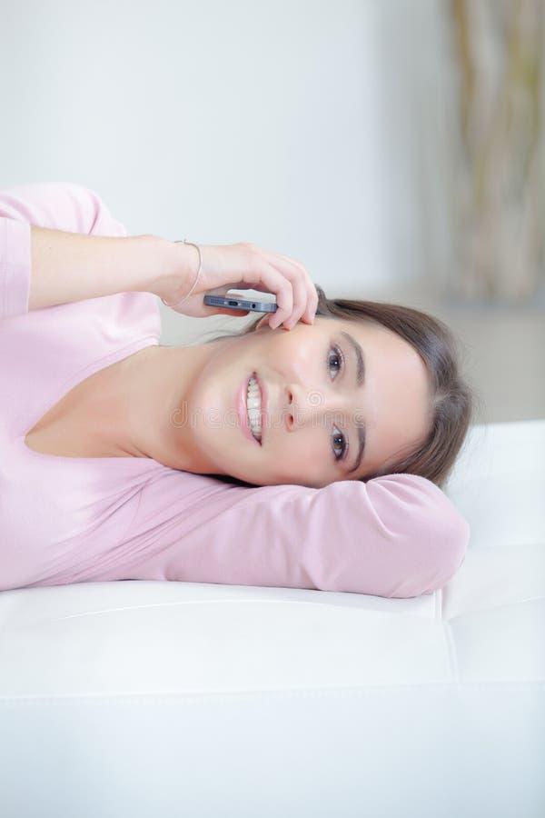 Νέα γυναίκα που βρίσκεται και που τηλεφωνά στοκ φωτογραφίες