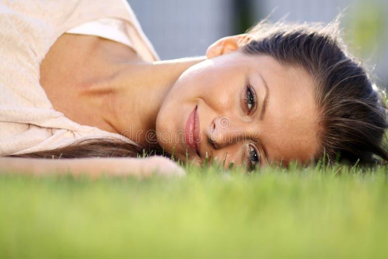 νέα γυναίκα που βρίσκεται σε έναν πράσινο χορτοτάπητα στοκ φωτογραφία