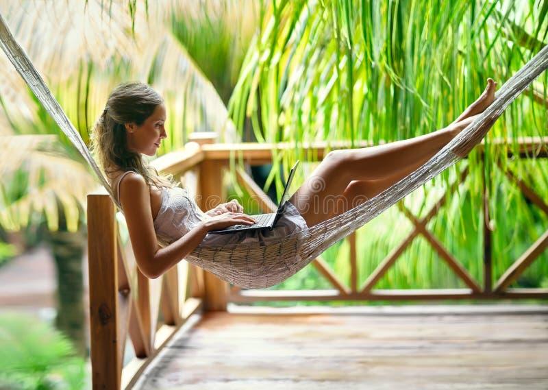 Νέα γυναίκα που βρίσκεται σε μια αιώρα με το lap-top στοκ εικόνα με δικαίωμα ελεύθερης χρήσης