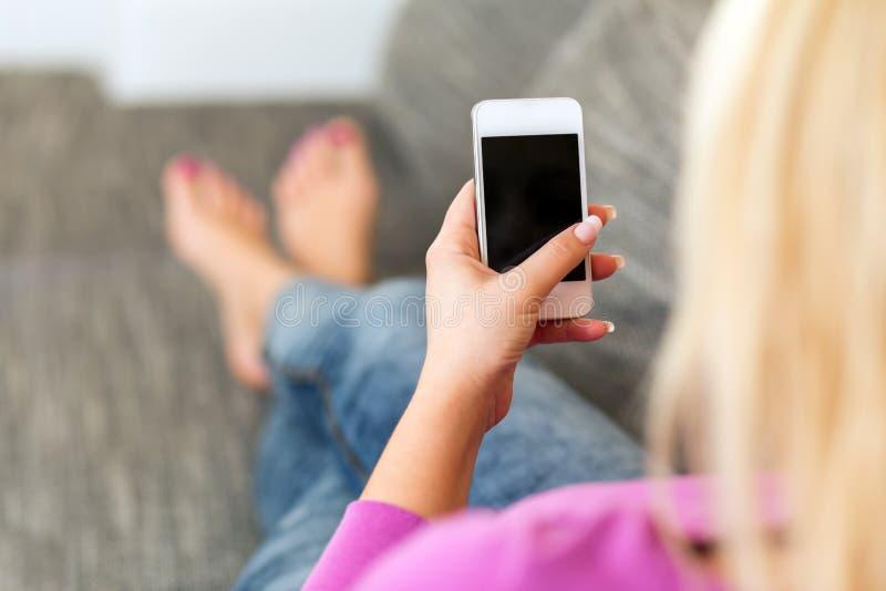 Νέα γυναίκα που βρίσκεται στον καναπέ με το κινητό τηλέφωνο στοκ εικόνες