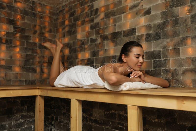 Νέα γυναίκα που βρίσκεται στον ξύλινο πάγκο στην αλατισμένη σάουνα στοκ εικόνες