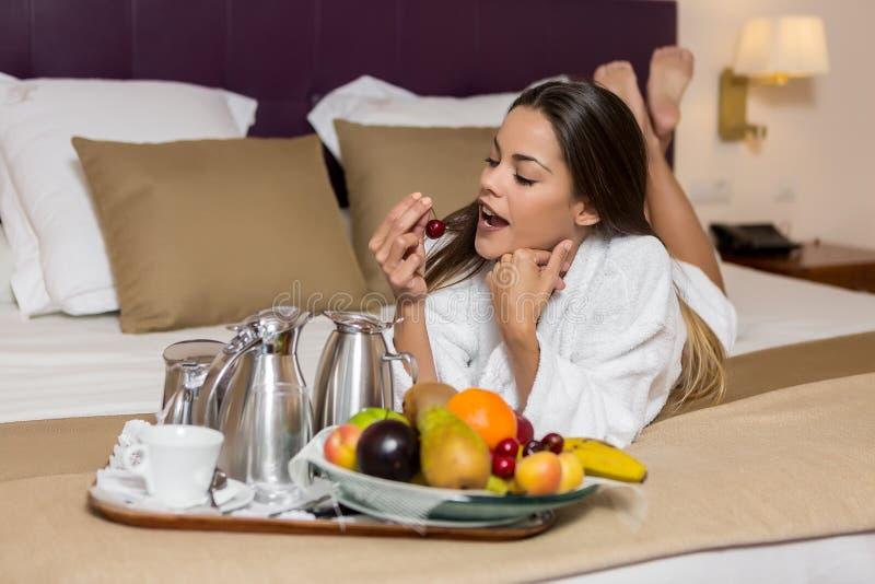 Νέα γυναίκα που βρίσκεται στο κρεβάτι και που τρώει τα φρούτα στοκ εικόνα