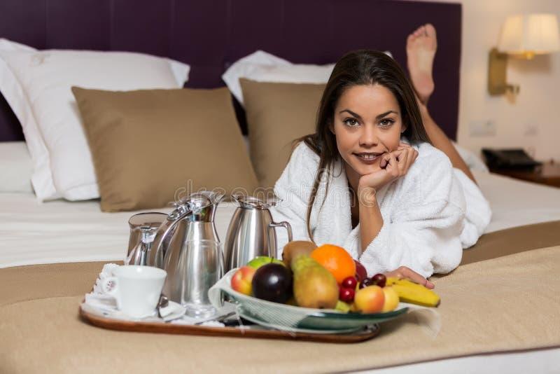 Νέα γυναίκα που βρίσκεται στο κρεβάτι με τα φρούτα και το σύνολο καφέ που τοποθετείται πλησίον στοκ εικόνα