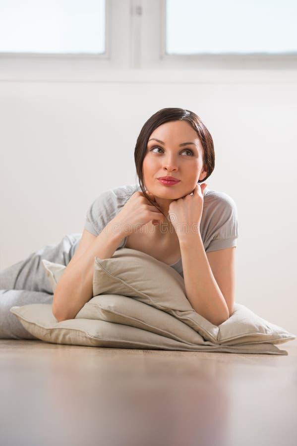 Νέα γυναίκα που βρίσκεται στο πάτωμα με τα μαξιλάρια στοκ εικόνες